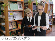 Купить «Pupil in black jacket and sunglasses and schoolgirl,holding book, read it on background of shelves with books», фото № 25837915, снято 20 марта 2015 г. (c) Losevsky Pavel / Фотобанк Лори