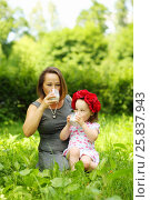 Купить «Little girl in flower wreath and her mother drink milk in summer park», фото № 25837943, снято 24 июня 2015 г. (c) Losevsky Pavel / Фотобанк Лори