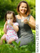 Купить «Little girl in wreath drink milk and her mother smiles in summer park», фото № 25837951, снято 24 июня 2015 г. (c) Losevsky Pavel / Фотобанк Лори