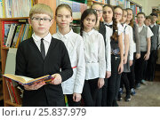 Купить «Eleven students in school library are to each other, boy in foreground holding book in his hands, everyone is looking at camera, focus on boy left», фото № 25837979, снято 20 марта 2015 г. (c) Losevsky Pavel / Фотобанк Лори