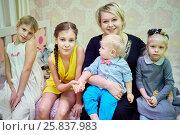 Купить «Smiling woman and four children sit on couch in room», фото № 25837983, снято 21 ноября 2015 г. (c) Losevsky Pavel / Фотобанк Лори