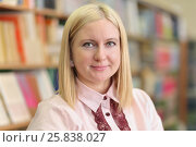 Купить «Teacher in pink shirt on background of shelves with books, smiling», фото № 25838027, снято 20 марта 2015 г. (c) Losevsky Pavel / Фотобанк Лори