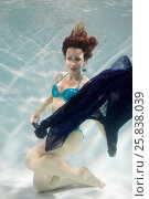 Купить «Smiling young woman in blue swimsuit poses in swimming pool with dark-blue fabric in hands underwater», фото № 25838039, снято 14 мая 2016 г. (c) Losevsky Pavel / Фотобанк Лори