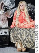 Купить «Woman with long blond hair in red dress sits on bed», фото № 25838135, снято 21 мая 2015 г. (c) Losevsky Pavel / Фотобанк Лори