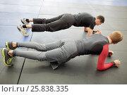 Купить «Man and coach do slat exercise on floor in sport club», фото № 25838335, снято 2 апреля 2016 г. (c) Losevsky Pavel / Фотобанк Лори
