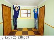 Купить «Boy and girl pose in room with optical illusion», фото № 25838359, снято 24 марта 2015 г. (c) Losevsky Pavel / Фотобанк Лори