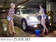 Купить «Two young smiling women water with hose car in underground parking», фото № 25838383, снято 13 февраля 2015 г. (c) Losevsky Pavel / Фотобанк Лори