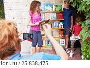 Купить «MOSCOW, RUSSIA - JUN 26, 2015: Family of three poses to photographer at porch of children library 16. Books for summer reading are on the shelf.», фото № 25838475, снято 26 июня 2015 г. (c) Losevsky Pavel / Фотобанк Лори