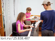 Купить «Mother plays piano, son turns over leaves of printed music and daughter reads book at room», фото № 25838487, снято 26 июня 2015 г. (c) Losevsky Pavel / Фотобанк Лори