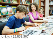 Купить «Mother and two children sit and read books in reading room of children library, focus on mother», фото № 25838507, снято 26 июня 2015 г. (c) Losevsky Pavel / Фотобанк Лори