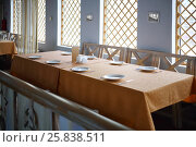Купить «Table with serving, wooden seats in empty canteen at sunny day», фото № 25838511, снято 5 апреля 2016 г. (c) Losevsky Pavel / Фотобанк Лори