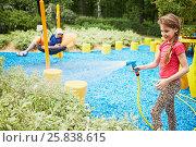 Купить «Little girl waters from hose with spray plants in summer park», фото № 25838615, снято 26 июня 2015 г. (c) Losevsky Pavel / Фотобанк Лори