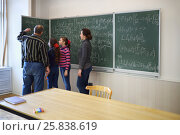 Купить «Two teachers and two girls stand near blackboard with formulas in classroom», фото № 25838619, снято 7 апреля 2016 г. (c) Losevsky Pavel / Фотобанк Лори