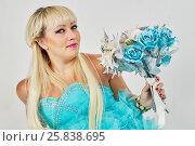 Купить «Smiling woman in blue fluffy dress with bunch of artificial flowers», фото № 25838695, снято 29 марта 2015 г. (c) Losevsky Pavel / Фотобанк Лори