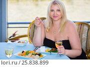 Купить «Blonde woman sitting at table in ship restaurant, eating and drinking wine», фото № 25838899, снято 25 августа 2015 г. (c) Losevsky Pavel / Фотобанк Лори