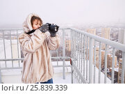 Купить «Woman in fur jacket takes pictures of city standing on building roof in winter», фото № 25839339, снято 15 февраля 2015 г. (c) Losevsky Pavel / Фотобанк Лори