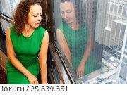 Купить «Woman sit on a windowsill looking out the window at New York street», фото № 25839351, снято 22 августа 2014 г. (c) Losevsky Pavel / Фотобанк Лори