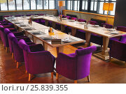 Купить «RUSSIA, MOSCOW - DEC 28, 2014: Hall with served tables with plate Reserved and violet soft armchairs in restaurant Siren (Lilac) in Sokolniki park», фото № 25839355, снято 28 декабря 2014 г. (c) Losevsky Pavel / Фотобанк Лори
