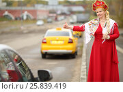 Купить «Woman in traditional russian clothes and kokoshnik with long braid hitchhikes», фото № 25839419, снято 15 октября 2015 г. (c) Losevsky Pavel / Фотобанк Лори