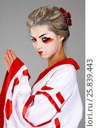 Купить «Girl in traditional Japanese costume and makeup standing with hands clasped studio shot», фото № 25839443, снято 17 ноября 2014 г. (c) Losevsky Pavel / Фотобанк Лори