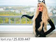 Купить «Pretty blonde woman with black cats ears poses on balcony at autumn day», фото № 25839447, снято 15 октября 2015 г. (c) Losevsky Pavel / Фотобанк Лори