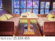 Купить «Table with plate Reserved and two sofas near window in cafe», фото № 25839455, снято 28 декабря 2014 г. (c) Losevsky Pavel / Фотобанк Лори