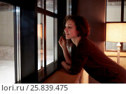 Купить «Young curly woman looks in window leaning her elbows on windowsill in room with torchiere», фото № 25839475, снято 28 декабря 2014 г. (c) Losevsky Pavel / Фотобанк Лори
