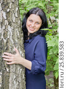 Купить «Portrait of smiling dark-haired woman peeking out from behind the tree in green summer park», фото № 25839583, снято 22 мая 2016 г. (c) Losevsky Pavel / Фотобанк Лори
