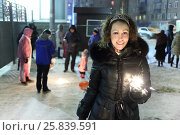 Купить «Young woman holding sparkler in foreground, in background, people celebrate new year, woman in focus», фото № 25839591, снято 1 января 2015 г. (c) Losevsky Pavel / Фотобанк Лори