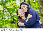 Купить «Half-length portrait of teenage girl and dark-haired wooman standing embraced in summer park», фото № 25839599, снято 22 мая 2016 г. (c) Losevsky Pavel / Фотобанк Лори