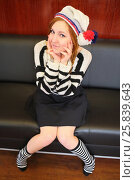 Купить «Girl with braces in a white hat with a pompom and a striped sweater and socks sits on a chair», фото № 25839643, снято 21 февраля 2015 г. (c) Losevsky Pavel / Фотобанк Лори