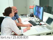 RUSSIA, MOSCOW - AUG 31, 2015: two doctors shows magnetic resonance exam procedure, view from control room in multidisciplinary Clinic Center Endosurgery and Lithotripsy (CELT) Редакционное фото, фотограф Losevsky Pavel / Фотобанк Лори