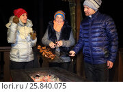 Купить «A man and two women doing barbecues and communicate on a winter evening», фото № 25840075, снято 22 февраля 2015 г. (c) Losevsky Pavel / Фотобанк Лори