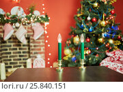 Купить «Interior of room with firtree decorated to christmas holidays, fireplace, red walls. Focus  on electric candles at table.», фото № 25840151, снято 9 января 2015 г. (c) Losevsky Pavel / Фотобанк Лори