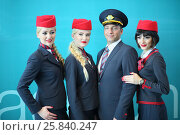 Купить «MOSCOW – JUL 09, 2015: Portrait of a crew of three beautiful flight attendants in red hat and one steward at DME RUNVAY in Domodedovo», фото № 25840247, снято 9 июля 2015 г. (c) Losevsky Pavel / Фотобанк Лори