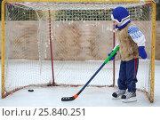 Купить «Little boy on skates with a hockey stick stands at the gate», фото № 25840251, снято 23 февраля 2015 г. (c) Losevsky Pavel / Фотобанк Лори