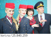 Купить «MOSCOW – JUL 09, 2015: A smiling flight attendant with colleagues under the golden rain at DME RUNVAY in Domodedovo», фото № 25840259, снято 9 июля 2015 г. (c) Losevsky Pavel / Фотобанк Лори