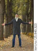 Купить «Portrait in full growth young man in gray coat with outstretched hands on alley in autumn park, looking up», фото № 25840323, снято 25 октября 2015 г. (c) Losevsky Pavel / Фотобанк Лори