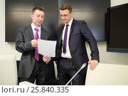 Купить «Two businessmen view documents standing with a blank sheet of paper near conference table», фото № 25840335, снято 10 апреля 2014 г. (c) Losevsky Pavel / Фотобанк Лори