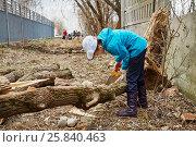 Купить «Girl saws old fallen tree outdoor at spring day», фото № 25840463, снято 18 апреля 2015 г. (c) Losevsky Pavel / Фотобанк Лори