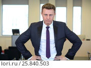 Portrait of young angry businessman with hands on hips in the office, фото № 25840503, снято 10 апреля 2014 г. (c) Losevsky Pavel / Фотобанк Лори