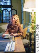 Купить «Middleaged blonde woman sits with tea and looks at camera in cozy restaurant», фото № 25840559, снято 12 июля 2015 г. (c) Losevsky Pavel / Фотобанк Лори