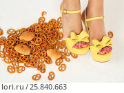 Купить «Female feet in yellow heels among sweets on white floor in studio», фото № 25840663, снято 3 сентября 2015 г. (c) Losevsky Pavel / Фотобанк Лори