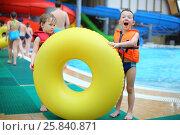 Купить «Two little boys in a life jacket near a big yellow swimming circle at the waterpark», фото № 25840871, снято 28 февраля 2015 г. (c) Losevsky Pavel / Фотобанк Лори