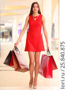 Купить «Beautiful smiling girl in short dress goes with bags in shopping center», фото № 25840875, снято 21 апреля 2015 г. (c) Losevsky Pavel / Фотобанк Лори