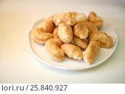 Купить «Pile of fresh and delicious mini croissants on a plate», фото № 25840927, снято 6 октября 2014 г. (c) Losevsky Pavel / Фотобанк Лори