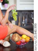 Купить «Woman in red dress lying on kitchen table with legs takes grapes», фото № 25840999, снято 4 июня 2015 г. (c) Losevsky Pavel / Фотобанк Лори
