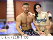 Купить «Portrait of a tanned man and light-skinned woman near pool with bathing people, focus on man», фото № 25841135, снято 28 февраля 2015 г. (c) Losevsky Pavel / Фотобанк Лори