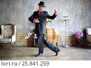 Купить «Young man in black suit and hat dances tango in stylish retro room», фото № 25841259, снято 4 июня 2015 г. (c) Losevsky Pavel / Фотобанк Лори