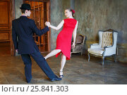 Beautiful girl in red dress and young man in hat dance tango in retro room, фото № 25841303, снято 4 июня 2015 г. (c) Losevsky Pavel / Фотобанк Лори